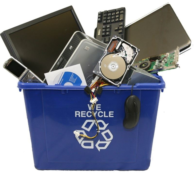 A blue recycling container brimming with old electronics like cell phones and computer parts.